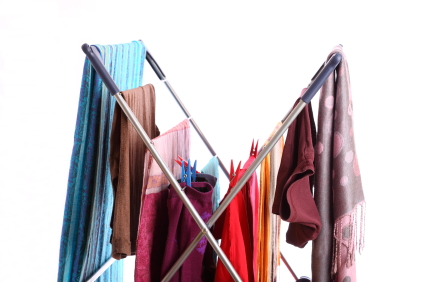 Colourful clothes hanging for drying on an airing rack