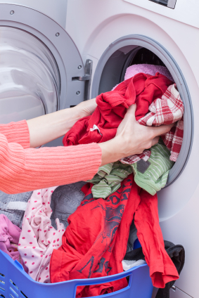 Picture of a woman removing clothes from a washing machine